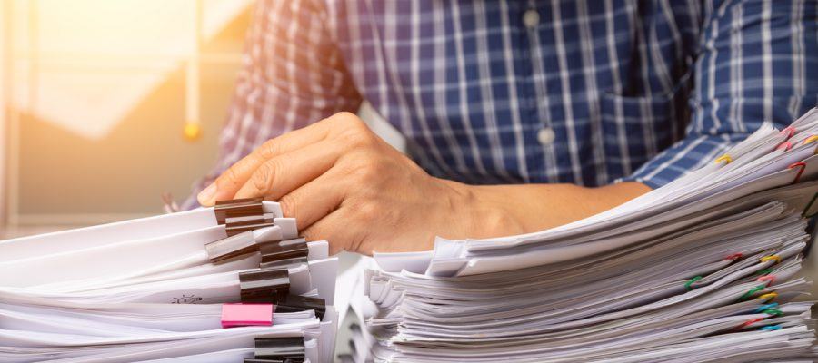 Business man hand pick up Stack overload document report paper.